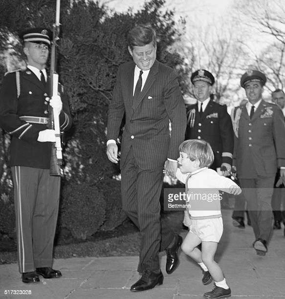 After attending ceremonies at Arlington National Cemetery John F Kennedy Jr smiles and skips hand in hand with his father as they pass a stoic...