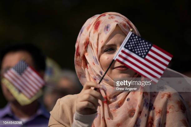 After becoming an American citizen Suad Alnababteh waves an American flag while 'America The Beautiful' is sung during a naturalization ceremony at...