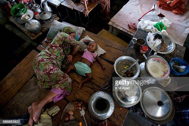 After being affected by the floodwater a woman with her child take shelter in the high school at Kurigram Bangladesh has been suffering from...