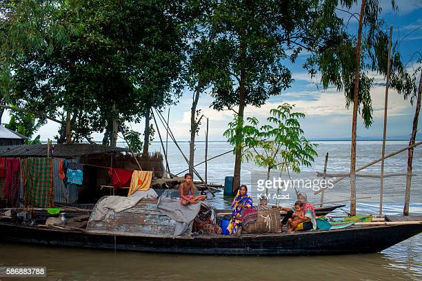 After being affected by the floodwater three family members take shelter on a boat at Kurigram Bangladesh has been suffering from devastating monsoon...