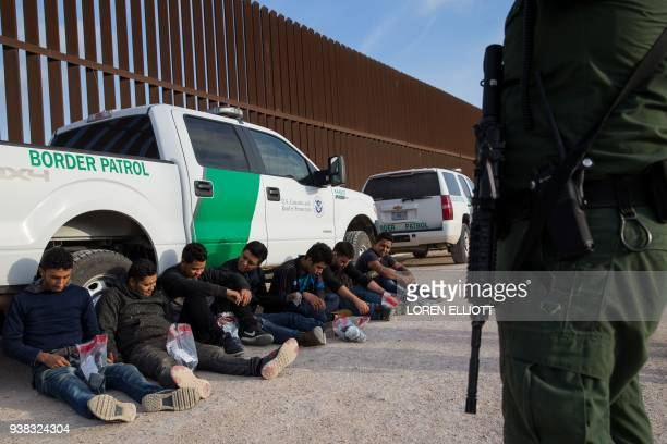 After being apprehended by Border Patrol illegal immigrants wait to be transported to a central processing center shortly after they crossed the...