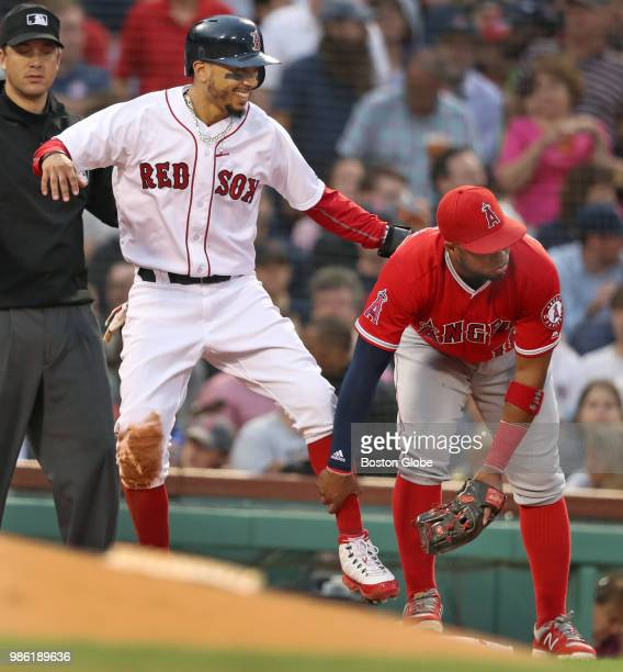 After Boston Red Sox player Mookie Betts left had slid safely into third base in the second inning Angels third baseman Luis Valbuena who does not...