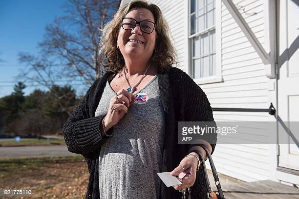 After casting her ballot resident Carolyn Virtue puts on her I voted sticker at the Canterbury town hall during the presidential election November 8...