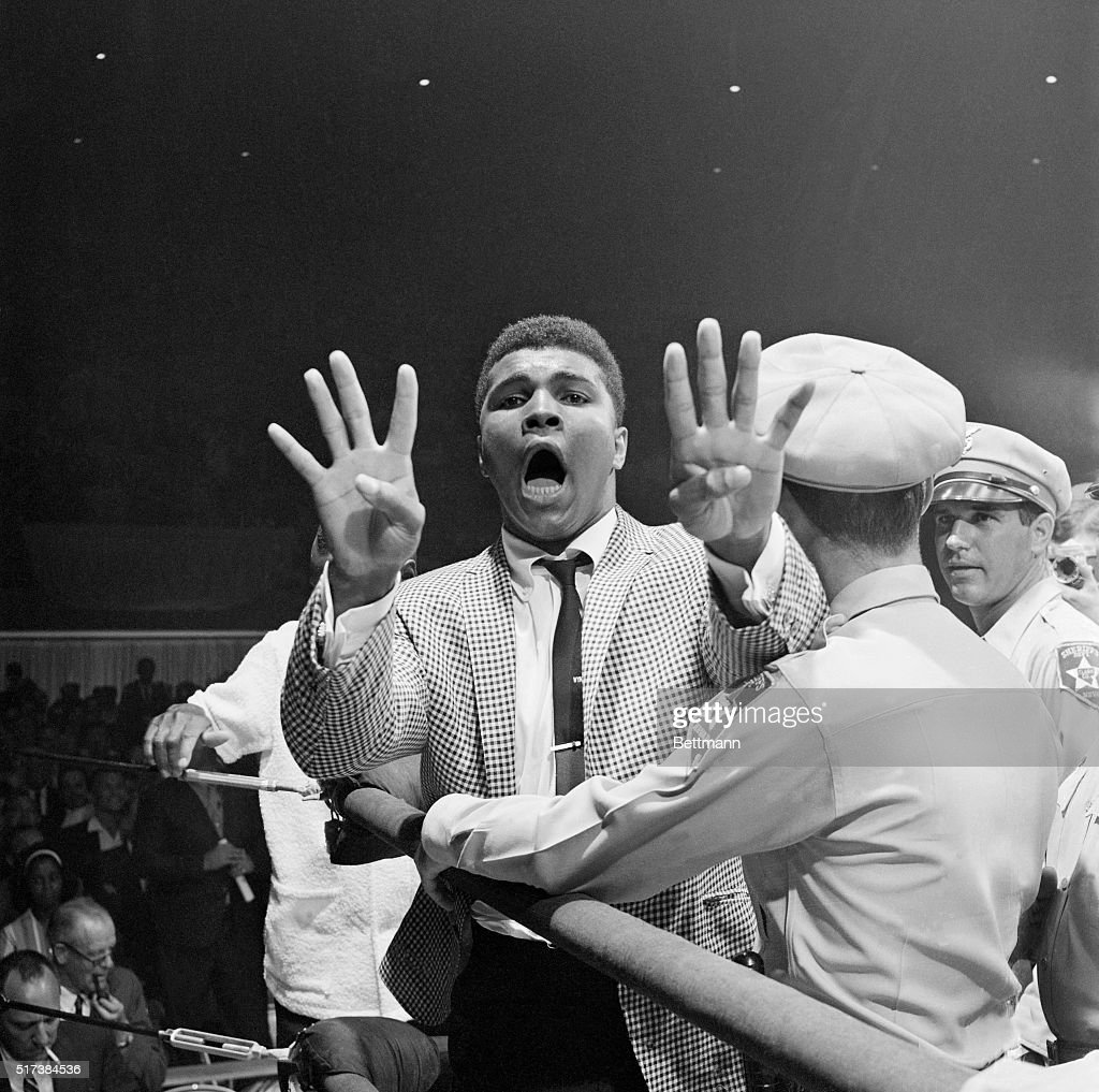 After Charles 'Sonny' Liston defeats Floyd Patterson in a World Heavyweight title fight, Muhammad Ali holds up eight fingers to indicate how many rounds it will take him to defeat Liston in their fight.