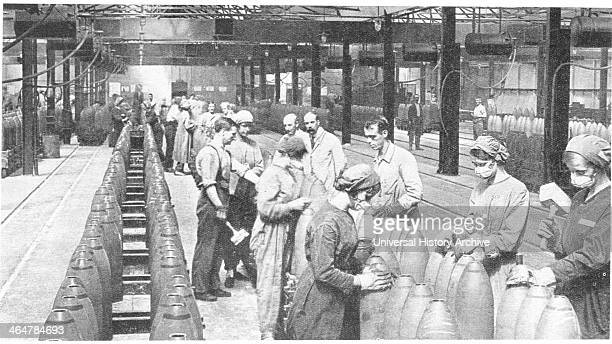 After conscription in 1916, British women took over many civilian jobs. Girls filling shells in a munitions factory, wearing masks and gloves to stop...