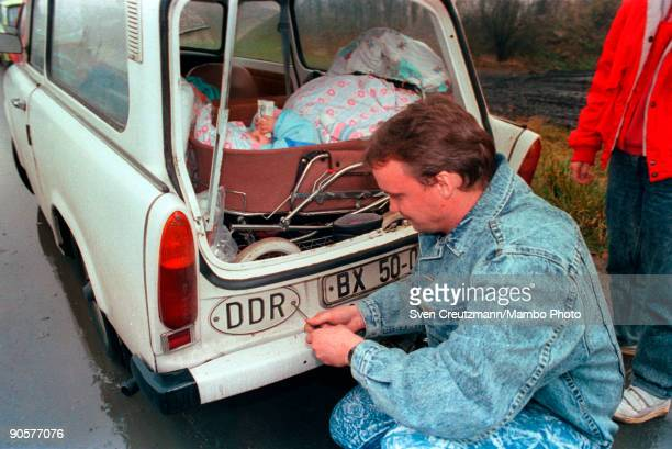 After crossing the border into West Germany and East German man kneels by the side of the road and unscrews the DDR plate from his car Schirnding...