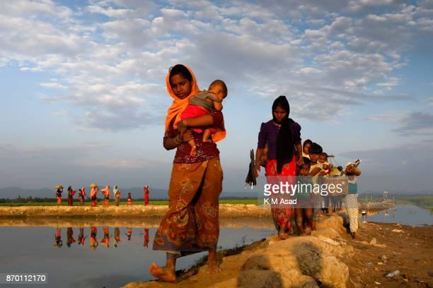 After crossing the Naf river Rohingya refugees walk to entered Bangladesh border area at Anjumanpara in Coxsbazar Bangladesh According to the UNHCR...