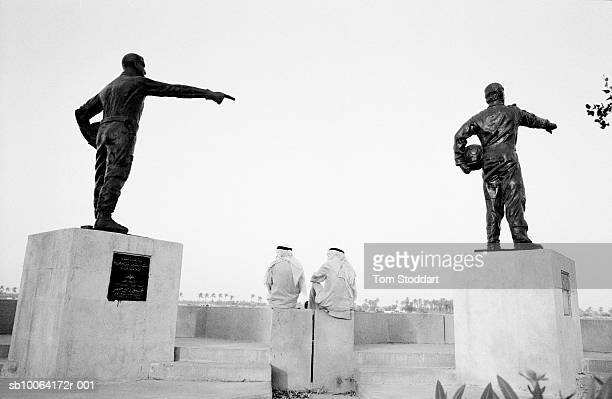 After fierce fighting a peaceful scene on the walkway of the Shatt Al Arab in Basrah where two men chat under the statues of Iraq's military heroes...