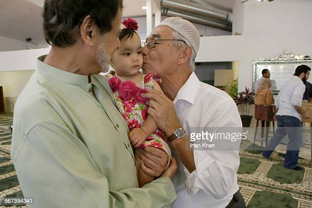 JULY 04 2014 After Friday prayers on July 04 2014 Rahmat Phyakul right plants a kiss on the cheeks of 1yearold Zaina Khan center held by her...