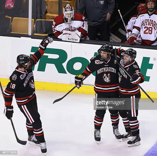 After giving up four goals in the first two periods, Harvard's starting goalie Raphael Girard, on bench at upper left, was pulled between periods,...