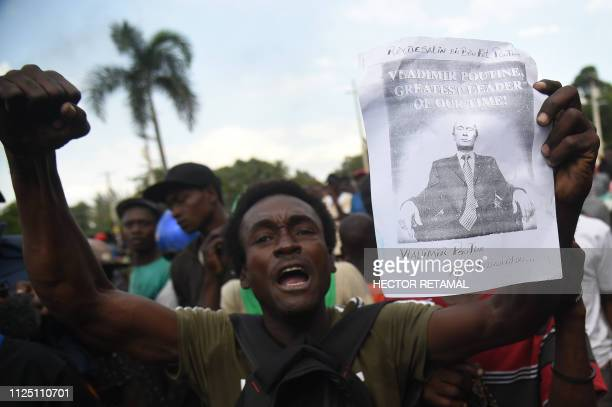 TOPSHOT After having burned a US flag protesters chants Long live Putin down with the Americans in the Haitian Capital PortauPrince February 15 on...