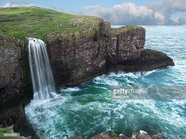After heavy rain, a fresh water stream plummets in a waterfall down a cliff face into the North Sea at Crawton in Aberdeenshire on the east coast of...