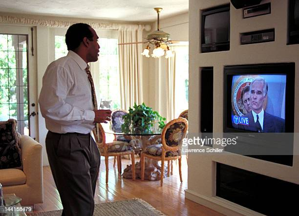 After his acquittal on double murder charges American former professional football player and actor OJ Simpson watches a television on which District...
