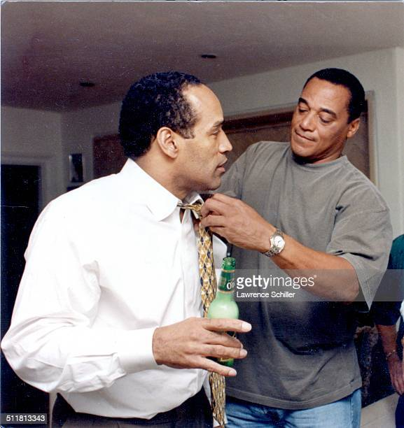 After his acquittal on double murder charges American former professional football player and actor OJ Simpson holds a bottle as his teammate Al...