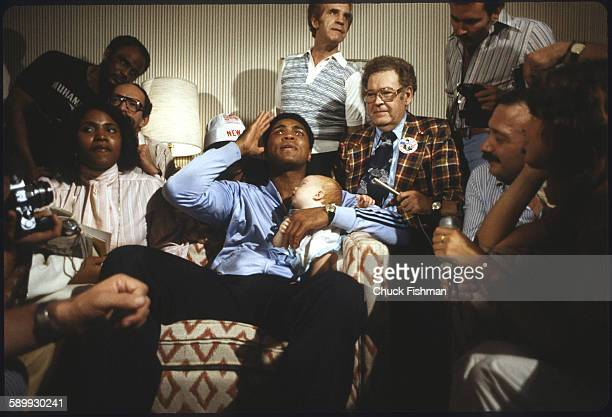 After his victory in a championship bout and surrounded by journalists and unidentified others American heavyweight boxer Muhammad Ali holds his...