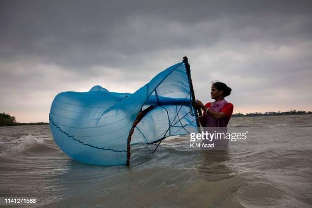 After hits Cyclone Fani in Bangladesh a woman catch's fish in the Shibsha River in Dakop Khulna