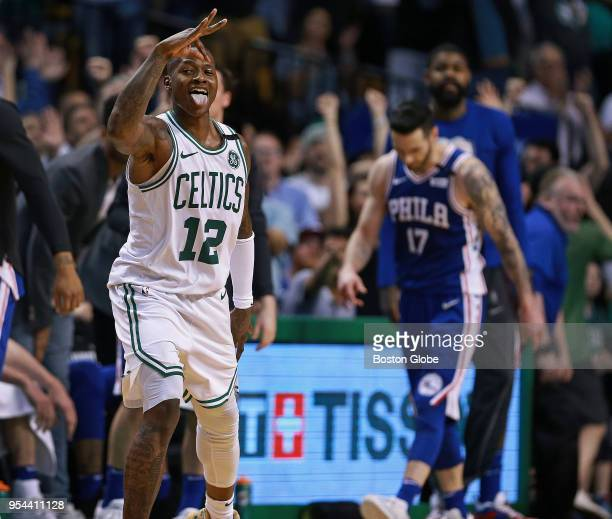After hitting a three pointer that put Boston ahead 9995 the Celtics Terry Rozier III reacts while Philadelphia 76ers JJ Redick is not as happy in...
