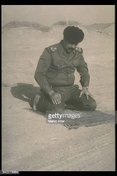 After Iraq's invasion of Kuwait Saddam Hussein prays in the Kuwait desert