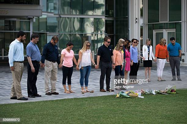 After laying flowers a group of people hold hands at the Dr Phillips Center for the Performing Arts in honor of the victims of the shooting at Pulse...
