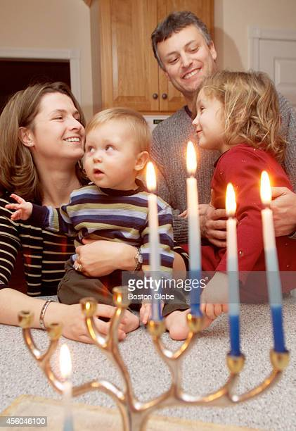 After lighting the Menorah on the fourth day of Hanukkah the Mair family Lisa and Glen holding their children William and Rachael get ready to open a...