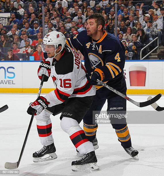 After losing his helmet Josh Gorges of the Buffalo Sabres defends against Jacob Josefson of the New Jersey Devils during an NHL game on December 15...
