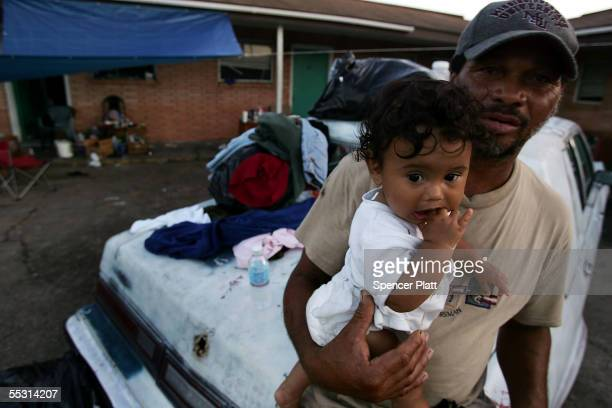 After losing their homes to Hurricane Katrina Julius Thompson holds Marcus Lemay 8 months a friends child while living in a ruined hotel September 7...