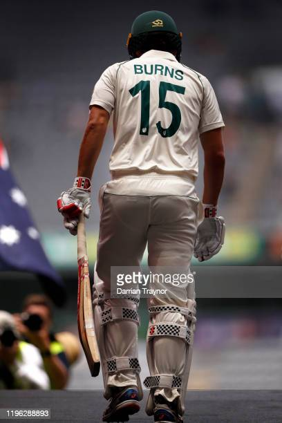 After making a duck in the first innings Joe Burns of Australia walks out to bat in the second innings during day three of the Second Test match in...