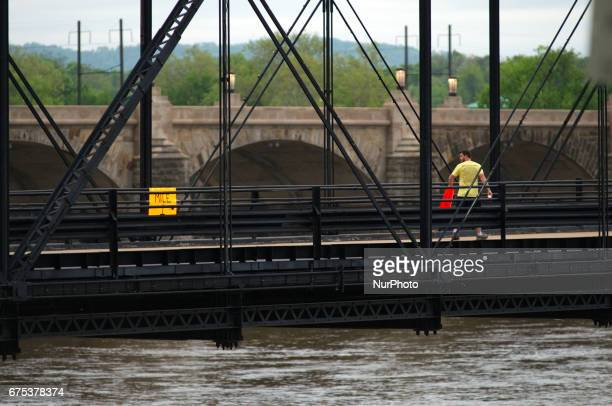 After mounting a onemile marker a man is seen looking over his shoulder as he continues his way on the Walnut St Bridge over the Susquehanna River in...