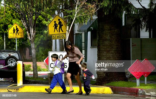 After picking up a student from Davis Elementary School in Santa Ana baby sitter Maria Castillo center crosses French Street which is blocked by...
