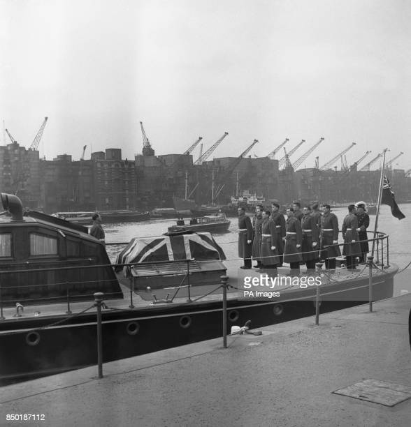 After placing the flagdraped coffin of Sir Winston Churchill on board the Havengore the Grenadier Guards bearer party stands to attention on the deck...