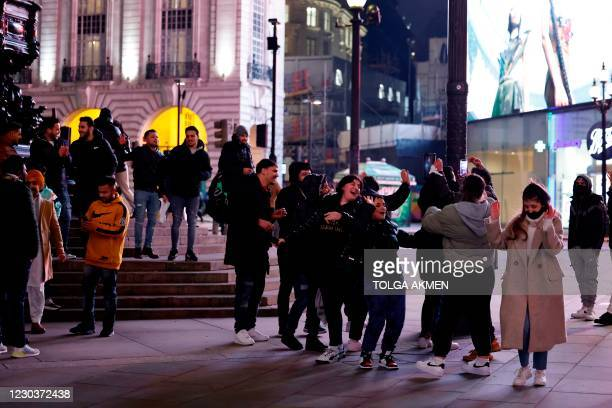 After police officers and stewards leave, groups of people gather together at Piccadilly Circus in a near-deserted London on New Year's Eve, December...