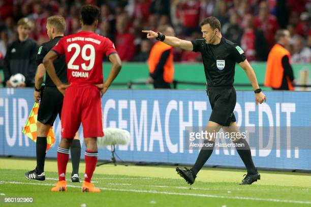 After reviewing a disallowed goal in the video area referee Felix Zwayer decides the goal was good during the DFB Cup final between Bayern Muenchen...