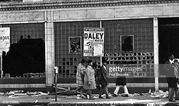 After riots erupted in response to the killing of civil rights leader Martin Luther King Jr residents walk past the rubble and broken windows of a...