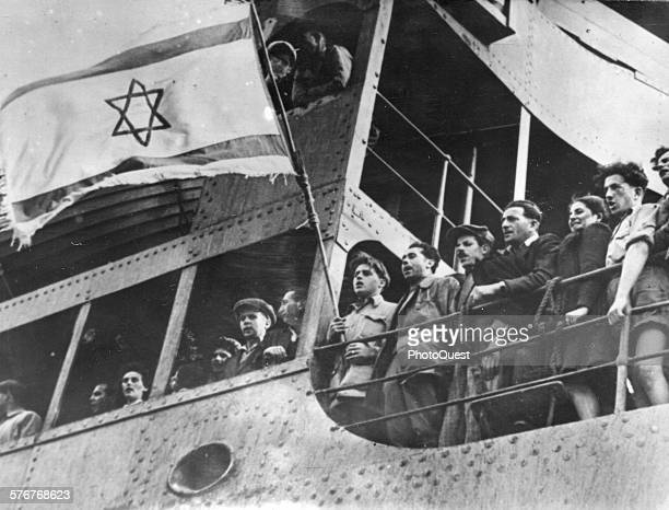 After sailing from Cypress to Palestine 297 Jewish refugee men women and children sing with joy as they arrive in the port of Haifa Isreal December 9...