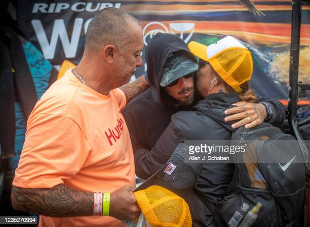 After saying a prayer together, Filipe Toledo, of Brazil, is hugged by his parents, Ricardo Toledo and Mari Toledo, before his match with fellow...