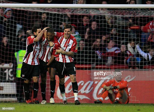 After scoring the opening goal Carl Cort of Brentford celebrates with his team mates infront of a dejected Charlton Athletic goalkeeper Rob Elliot...