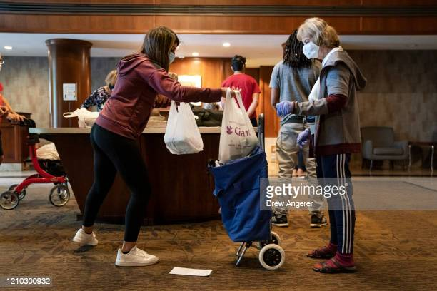 After shopping for the groceries, Hannah Vohra does a no-contact delivery for senior residents at a residential complex on April 17, 2020 in North...
