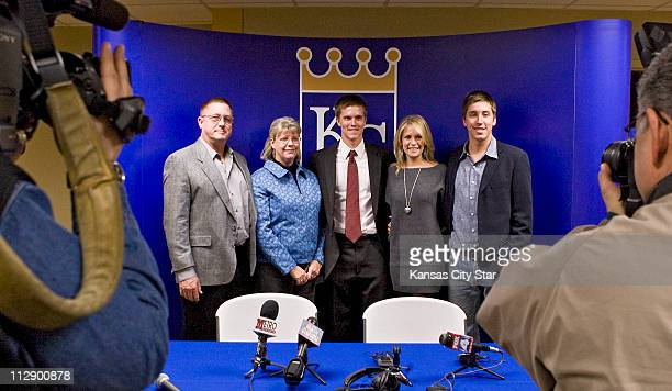 After signing a new fouryear contract with the Kansas City Royals pitcher Zack Greinke center poses for a photograph with his parents Don and Marsha...