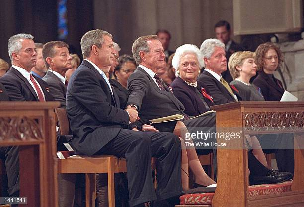 After speaking at the service for America's National Day of Prayer and Remembrance US President George W Bush grasps the hand of his father former...