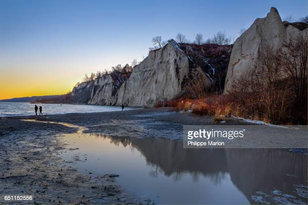 after sunset on a cold winter day a silhouetted couple walks by lake ontario and scarborough bluffs, toronto - lake ontario stock pictures, royalty-free photos & images