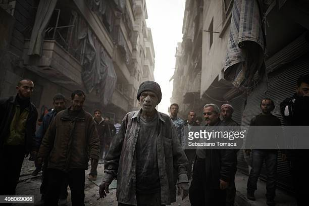 After surviving the collapse of his home a civilian walks away from the scene of a regime airstrike that destroyed his home March 20 2013