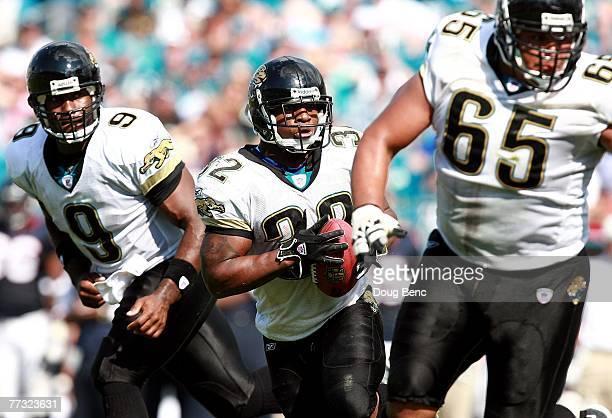 After taking the handoff from quarterback David Garrard running back Maurice JonesDrew of the Jacksonville Jaguars follows the lead block of...