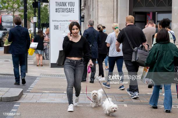After the announcement that Covid rules are to be relaxed by the government on July 19th, a woman crosses Oxford Circus with two pet dogs in the West...
