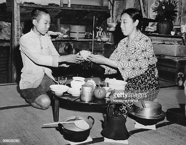 After the bombing of Tokyo, a Japanese mother and her 9 years old son having their midday meal in an emergency shelter outside Tokyo, Japan, on...