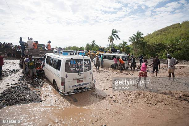 After the bridge in Ti Goave collapsed because of the hurricane people try to walk or drive through the river to continue on the road from north to...