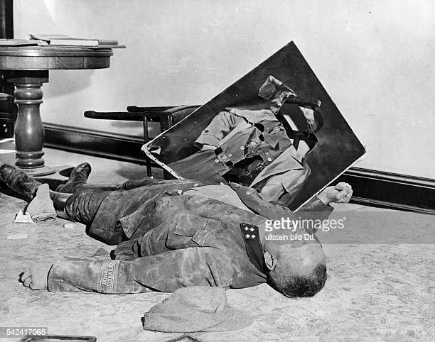 After the capture of Leipzig by the 1st US Army on April 19 1945 the dead body of an SS man who committed suicide next to a destroyed picture of...