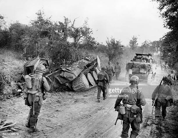 After the capture of SaintLo US infantry on the advance through Normandy towards Brittany on the roadside destroyed tanks and other war material of...