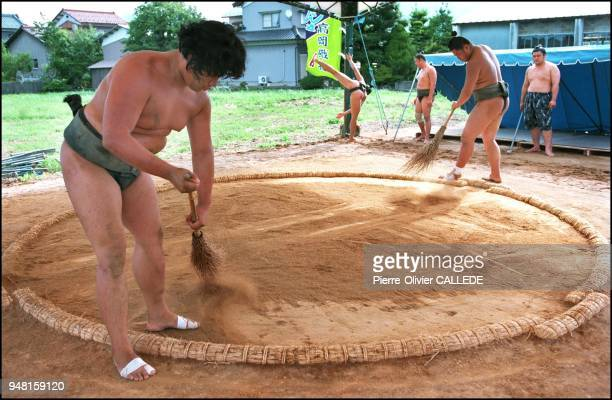 After the daily training session the lesser ranking clean the dohyo They pile the sand into the center of the circle planting a shinto rod into the...