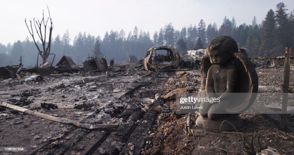 After the Fire Destroyed Everything, A Stone Sculpture of an Angel Endures, Watching over the Ash, Rubble, and Wrecked Vehicle in the Neighborhood : Stock Photo