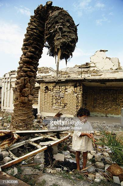 After the first Gulf conflict a child plays outside the bomb-damaged house where she lives in Basra.